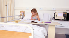 Little girl sitting in hospital bed colouring Stock Footage