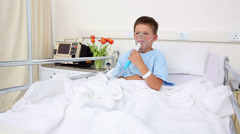 Little sick boy sitting in bed with oxygen mask Stock Footage