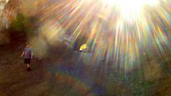 Man Emerges From Bronson Cave With Rainbow Sun Flare Stock Footage