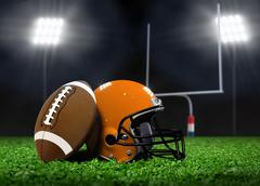 football ball and helmet on grass under spotlights - stock illustration