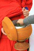 Put offerings in a buddhist monk's alms bowl, thailand Stock Photos