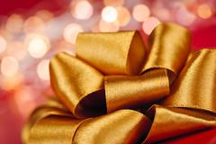 gold gift bow with festive lights - stock photo