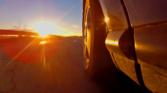 Beautiful low angle view of sport car race with sunset rays shining on tire, Stock Footage