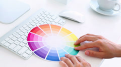 Graphic designer using colour wheel at his desk Stock Footage