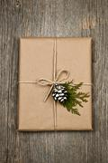 christmas present in brown paper tied with string - stock photo