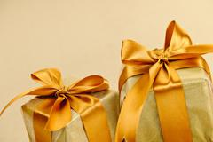 two golden wrapped gift boxes - stock photo
