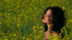 Ecology. Thoughtful woman is in a field of Raps. Stock Footage