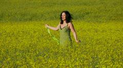 Lovely lady in green sun-dress walks in a field of Raps. Stock Footage