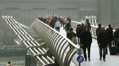 People walking over Millennium bridge in London. Stock Footage