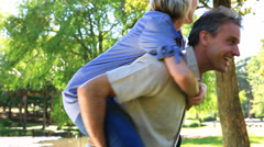 Happy man giving his partner a piggy back - stock footage