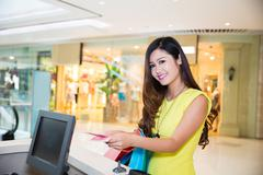 Young adult woman paying currency for purchases Stock Photos
