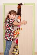 Panic little girl trying to close the closet Stock Photos