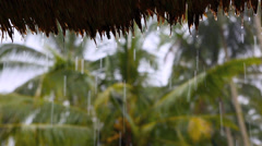 Rain drops dripping from thatched roof in heavy tropical rainy season downpour - stock footage