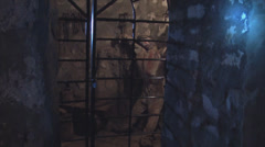 Wide shot of dummy of prisoner in chains behind grille Stock Footage