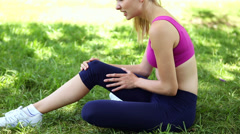 Injured fit blonde touching her knee on the grass - stock footage