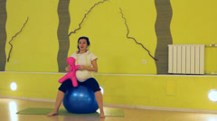 A pregnant woman with a doll doing exercises with the ball, yoga Stock Footage