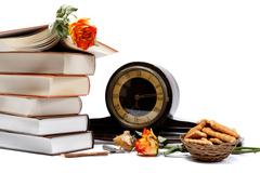 a stack of books, antique watches and cookies on a white background. - stock photo