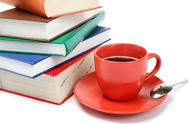 Stock Photo of a stack of books and a cup of coffee on a white background.