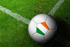 ireland flag pattern of a soccer ball in green grass - stock illustration