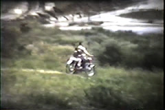 Man and child on motorcycles ride through field, early 1960's Stock Footage