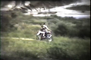 Stock Video Footage of man and child on motorcycles ride through field, early 1960's