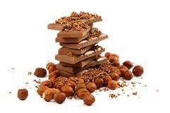 Stack of chocolate tiles with hazelnuts on a white background. Stock Photos