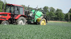Farm tractor with yellow tires ride through corn field work Stock Footage