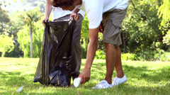 Happy volunteers picking up trash in the park Stock Footage