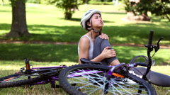 Fit girl touching her injured knee after a bike accident Stock Footage