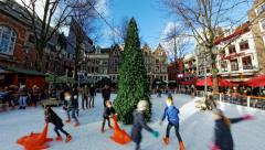 Dutch kids boys and girls enjoy ice skating around Christmas tree in rink Stock Footage