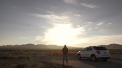 Man Leaves His Broken Down Car To Walk Into The Desert Stock Footage