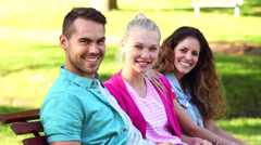 Students sitting together outside on a bench Stock Footage