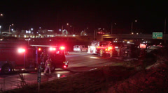 Firefighters at night bus fire aftermath along interstate Stock Footage