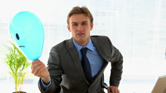 Grumpy businessman holding sad face balloon over face Stock Footage