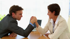 Business people arm wrestling at desk Stock Footage