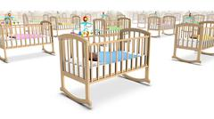 Angled close-up of endless Cribs with Baby - stock photo