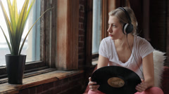Beautiful Teen Wearing Headphones Listens To Music And Looks At Her Record Stock Footage