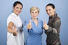 Successful  business women giving thumbs up - stock photo