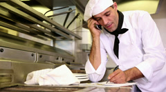 Handsome chef writing on clipboard while talking on phone Stock Footage