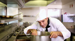 Handsome chef stirring a large pot Stock Footage