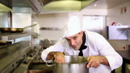 Stock Video Footage of Handsome chef stirring a large pot