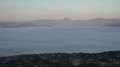 Weather, time-lapse, fog flowing over homes and city, sunrise, 4 hour span Stock Footage