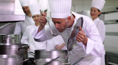 Head chef tasting pot of soup making ok sign Stock Footage