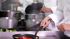 Chef frying vegetables then checking on colleague Stock Footage
