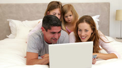 Parents and daughters lying on bed shopping online with laptop - stock footage
