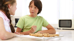 Siblings eating hot cookies from the cooling rack Stock Footage