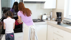 Mother and daughter taking hot cookies from the oven Stock Footage