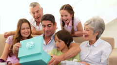 Extended family watching father open his present Stock Footage