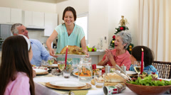Mother bringing turkey to dinner table for christmas - stock footage