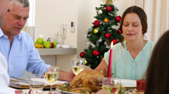 Extended family saying grace before christmas dinner - stock footage